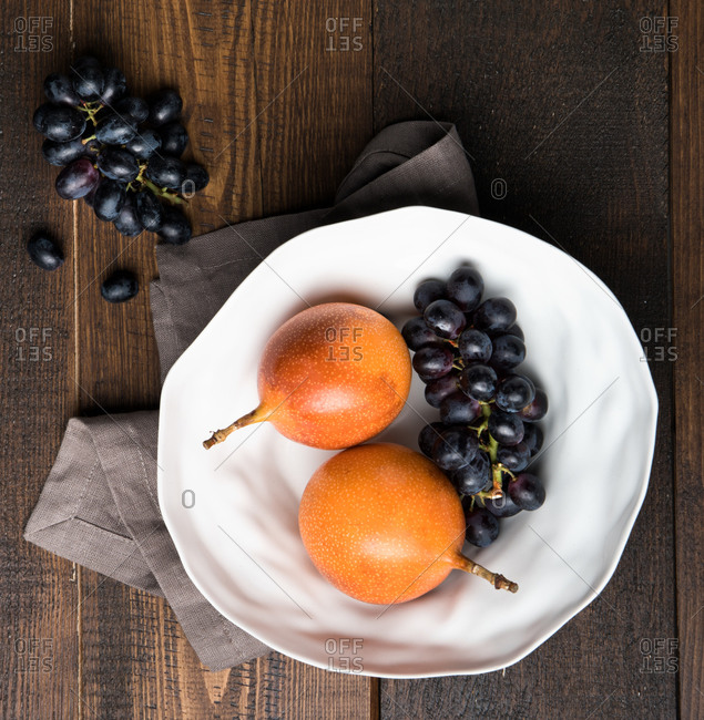 Top view of ripe passion fruits and bunches of purple grapes placed on wooden table in kitchen
