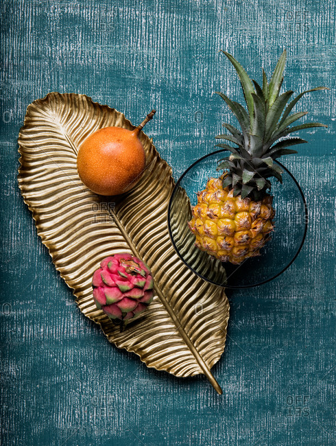 Top view of tasty passion fruits and pitaya on dish arranged with pineapple on blue table background