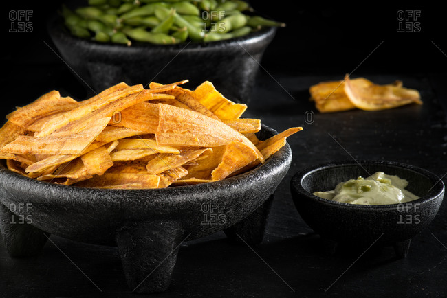 High angle of round bowls of various delicious appetizer such as fried plantains and edamame with guacamole on black table in modern restaurant