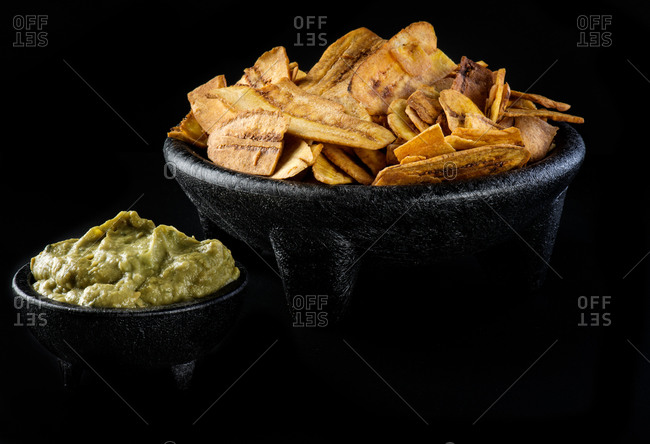 Bowl of fried plantains and guacamole on black table in modern restaurant
