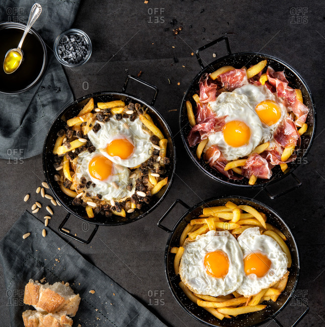 Top view of fried potato and eggs in black round pans with adding roasted ham or black pudding in composition with bread and ingredients on table in kitchen