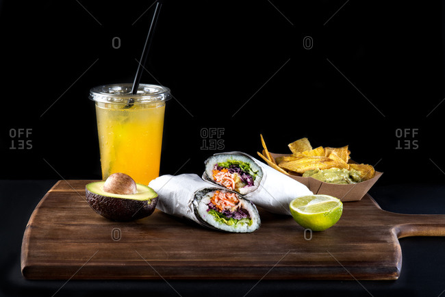 Set of typical Mexican snacks including fried plantains with guacamole and sushi burritos served with traditional cold fruit soda against black background