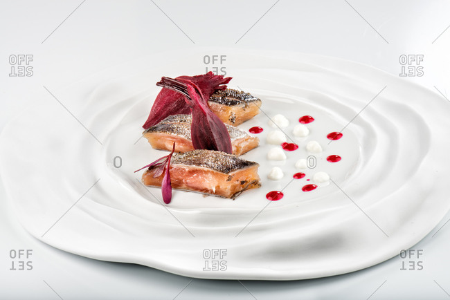 Fresh palatable snack of salmon fillet with vivid vinous herbs on round ceramic plate against white background in modern restaurant