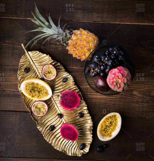 Top view of tasty passion fruits and pitaya on dish arranged with pineapple and purple grapes on wooden table
