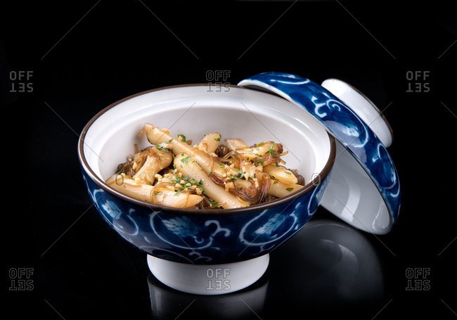 High angle of palatable dish of razor clams with onion and parsley in blue and white ceramic bowl placed on glossy surface with reflection against black background in studio
