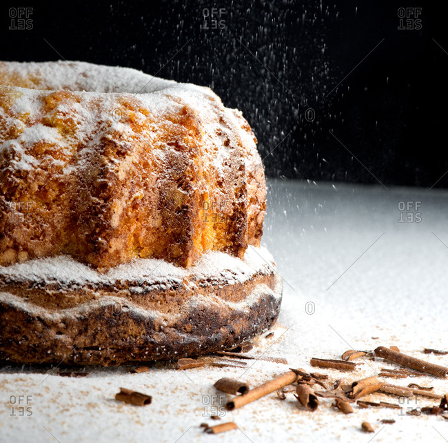Delicious soft biscuit with cinnamon in falling particles of sweet sugar powder on table
