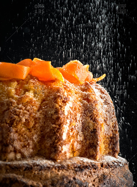 Delicious soft carrot cake with falling particles of sweet sugar powder on table