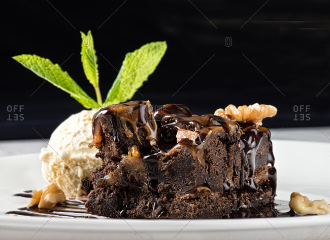Delicious chocolate brownie cake with milk ice cream and crushed nuts on plate
