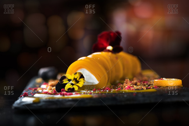 Served sophisticated snack of mango cannelloni filled with cream cheese and garnished with tender flowers