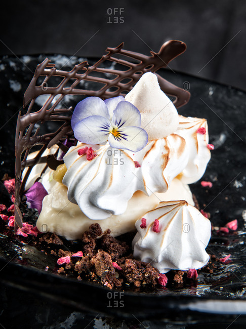 Delicious dessert made from meringue cookies decorated with violet flower and placed on plate with cream and chocolate