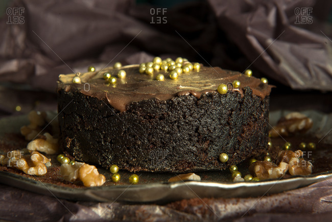 Chocolate cake with cream and golden chips placed against shabby background