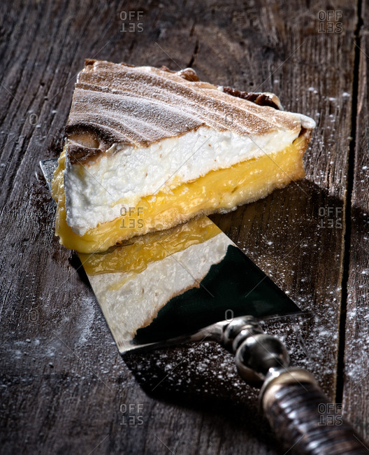 Vintage cake server with piece of juicy lemon pie with browned meringue layer