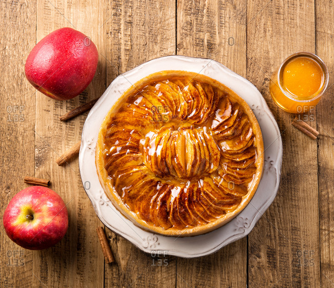 From above top view served whole pie with apples in syrup placed on plate among fresh apples on wooden table