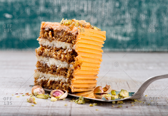 Cake server with piece of delicious carrot cake with pistachios on wooden table
