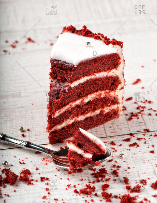 Slice of delicious red velvet cake on wooden table