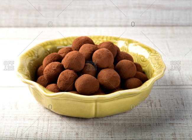 Yellow ceramic bowl with yummy homemade brown truffles made with chocolate powder placed on wooden counter