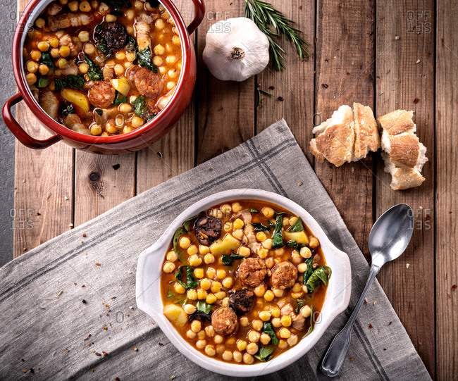 From above of served chickpea stew with chard and aromatic chorizo on timber background with towel