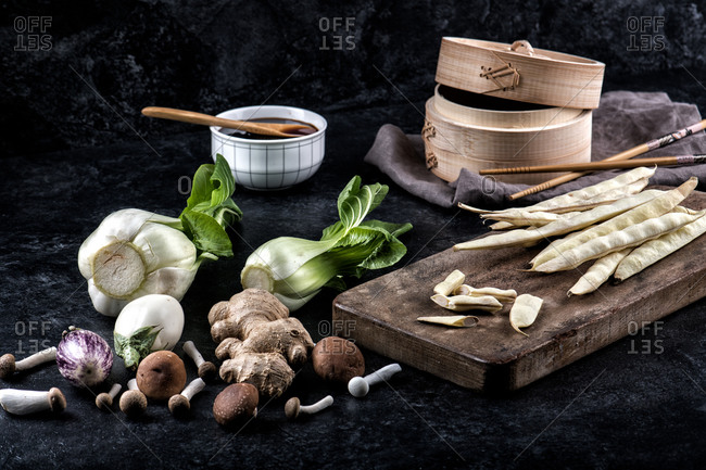Layout of assorted fresh vegetables and spices for Dim Sum ramen with soy sauce on black background