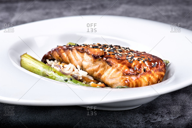 White ceramic plate with juicy steak of salmon in honey glaze with black and white sesame seeds