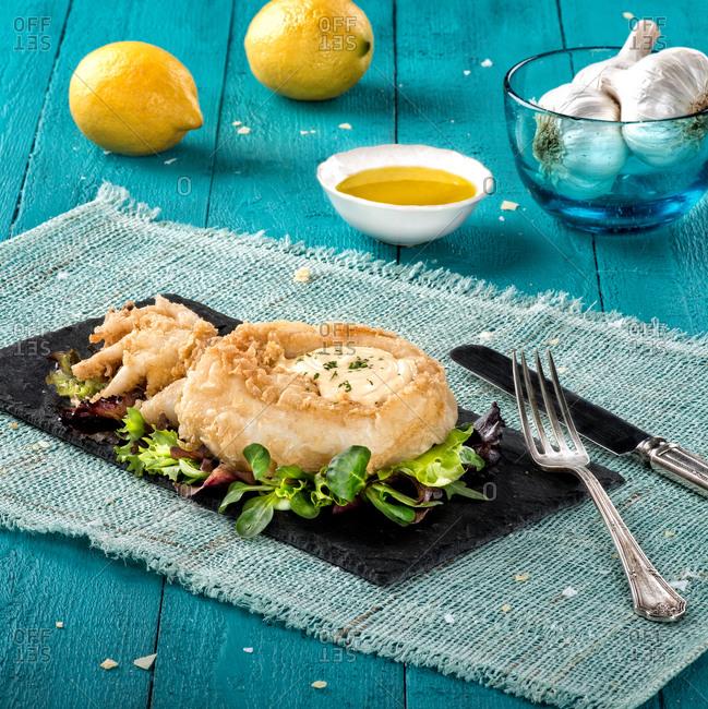 Served dish of cuttlefish fried with crumb coating and served with greens on black board with sauce and lemons on background