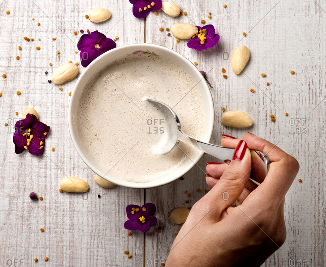 Top view of crop female eating tasty almond cream soup placed on table with violet flowers in luxury restaurant
