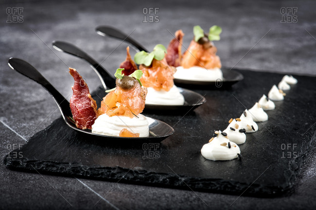 Portions of palatable smoked salmon and meat slices placed on slate board with cream cheese in luxury restaurant