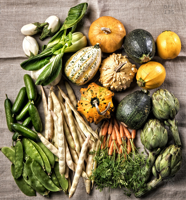 From above of harvest of various vegetables arranged on piece of fabric