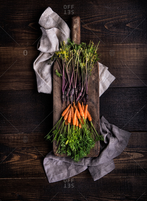 From above heaps of fresh purple and orange carrots on cutting board and natural fabrics on wooden rustic table