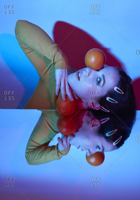 Sensual model leaning on mirror surface with fresh oranges in resting on face looking mysteriously at camera in blue illumination