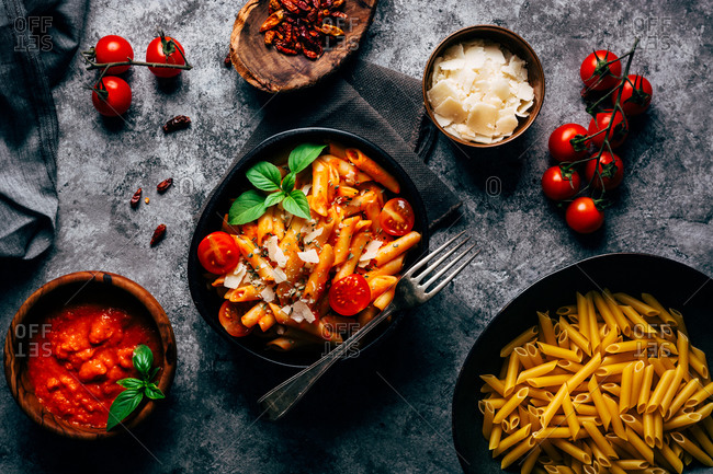 Top view of delicious pasta decorated with ripe cherry tomatoes and fresh basil near wooden bowl with arrabiata sauce and grated Parmesan cheese