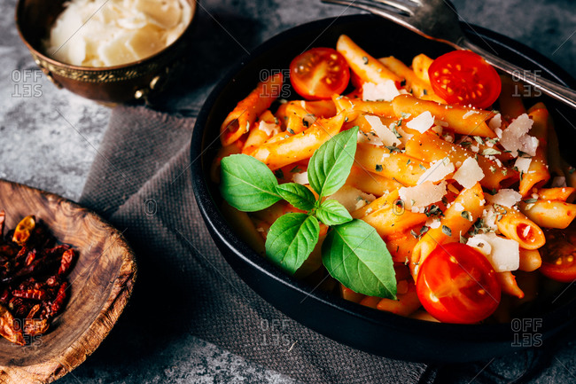 From above delicious pasta decorated with ripe cherry tomatoes and fresh basil near wooden bowl with arrabiata sauce and grated Parmesan cheese