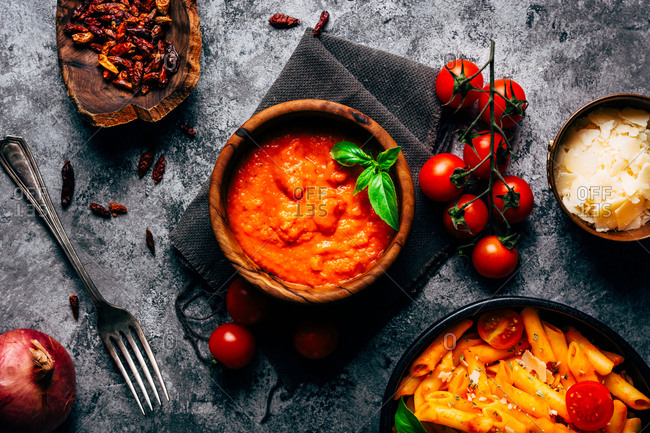 From above colorful arrabiata sauce in wooden bowl decorated with fresh basil near fresh cherry tomatoes and bowls with cheese and sun dried tomatoes and fresh delicious pasta decorated with ripe cherry tomatoes on shabby table with grey napkin