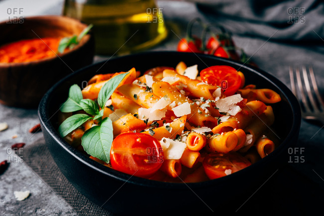 Delicious pasta decorated with ripe cherry tomatoes and fresh basil near wooden bowl with arrabiata sauce and grated Parmesan cheese