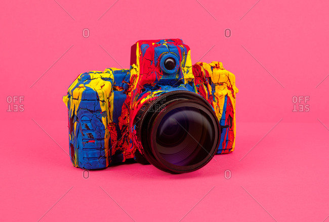 Creative retro photo camera painted with various colors arranged on colorful background