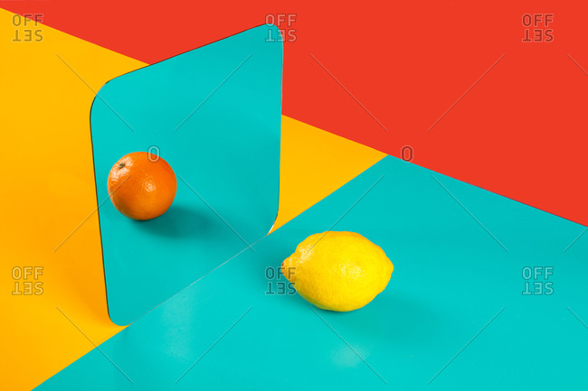 Vibrant background with mirror reflection of fresh orange as lemon on blue surface in composition with empty red and yellow areas like concept of perception in three dimensional space and distortion of imagination
