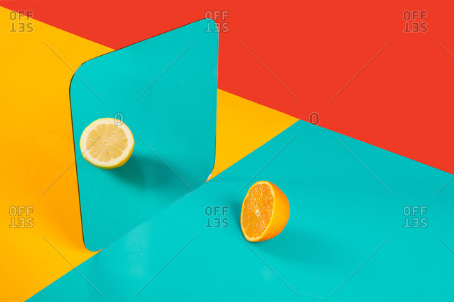 Vibrant background with mirror reflection of half of fresh orange as lemon on blue surface in composition with empty red and yellow areas like concept of perception in three dimensional space and distortion of imagination