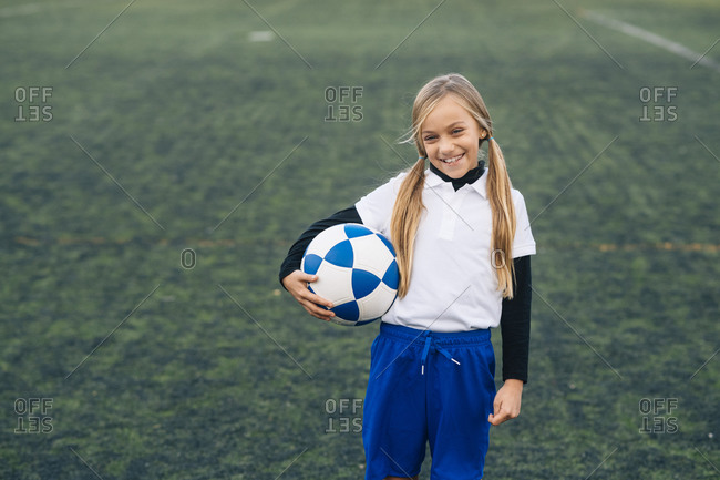 Cheerful preteen girl in white and blue uniform with soccer ball smiling at camera while standing alone on green field in modern sports club