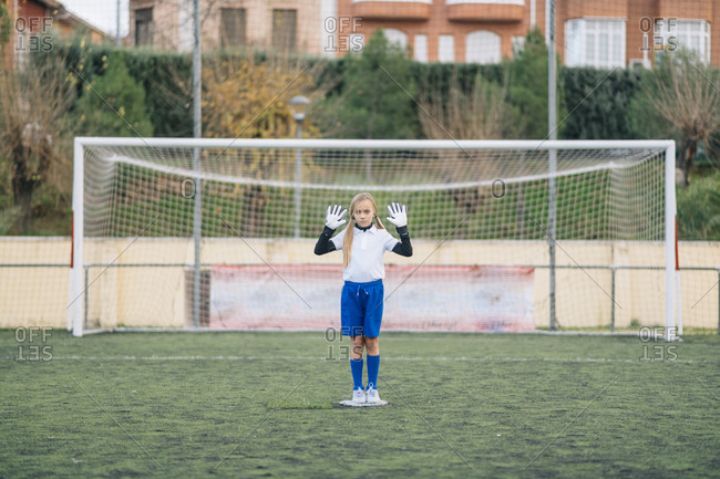 Serious preteen girl keeper in white and blue uniform defending soccer goal while standing with arms raised alone on field during match at modern outdoors stadium