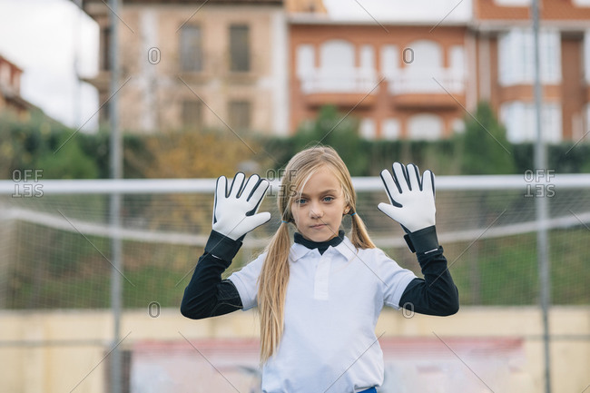 Full length serious preteen girl keeper in white and blue uniform defending soccer goal while standing with arms raised alone on field during match at modern outdoors stadium