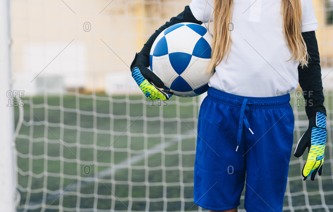 Crop girl in white and blue uniform with soccer ball while standing alone on green field in modern sports club