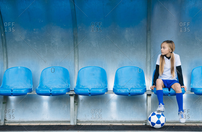 Full length frustrated preteen girl in soccer uniform sitting alone on blue plastic seat after match failure in sports club