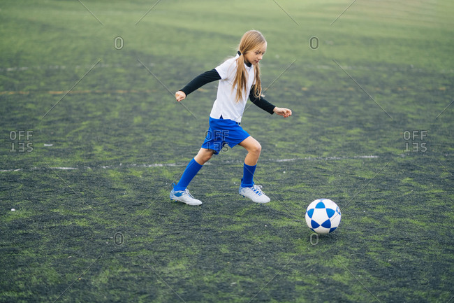 Side view of serious teenage girl in white and blue uniform and cleats running and preparing to kick ball while playing soccer alone on green field in contemporary sports club