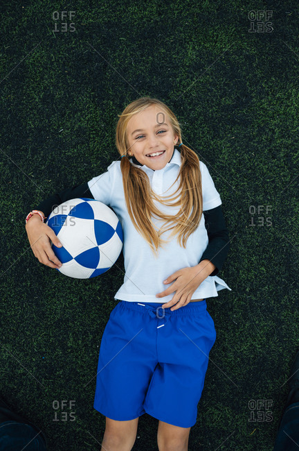 From above happy preteen girl with ponytails in uniform laughing while lying with ball on green field at football stadium