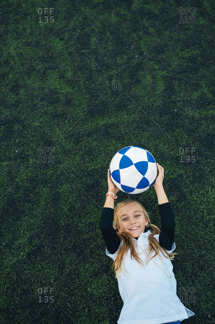 From above joyful preteen girl in white and blue uniform throwing soccer ball while lying alone on green field in modern sports club