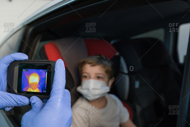 Crop doctor in medical gloves measuring temperature of boy while using infrared camera during coronavirus epidemic