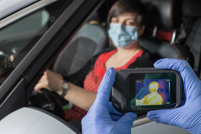 Crop doctor in medical gloves measuring temperature of female driver while using infrared camera during coronavirus epidemic