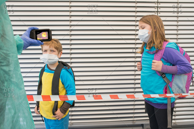 Crop medic in protective uniform using infrared camera for checking temperature of children in surgical masks on street during COVID 19 epidemic
