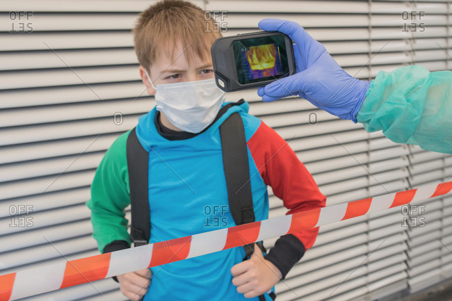 Unrecognizable medic in protective gloves and uniform using thermal imaging camera for checking temperature of kid on street during coronavirus outbreak