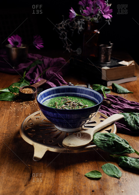 From above of ceramic bowl of fresh green smoothie with pumpkin seeds and sesame in composition with purple delicate fabric and bouquet of fresh violet Daisy flowers in vase placed on brown wooden table