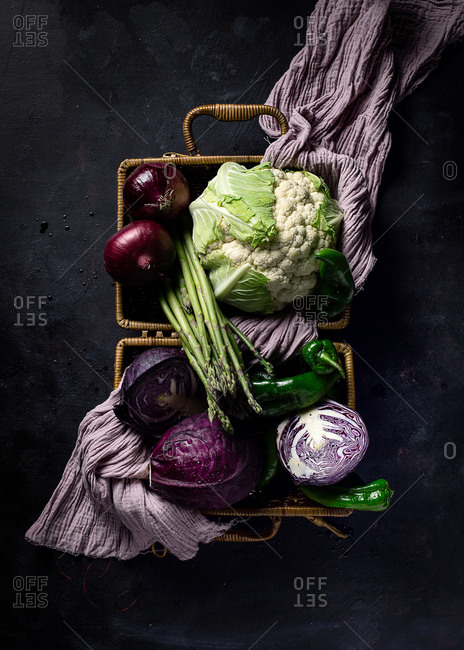 Top view of various fresh ripe vegetables with violet towel in wicker basket placed on dark surface as concept of healthy food